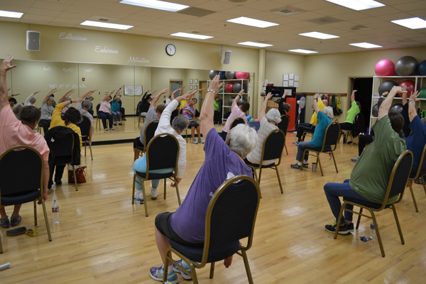 Participants Stretching in a Chair Yoga Class
