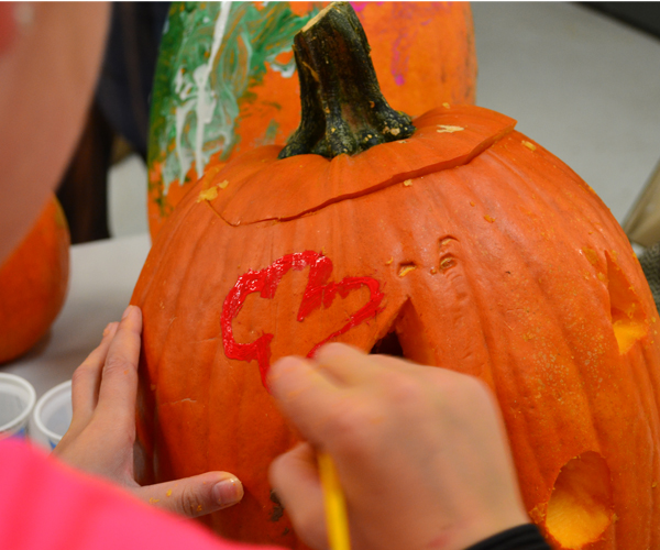 Young Child Painting Pumpkin