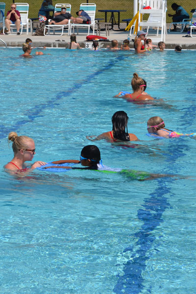 Group of children practicing their swimming skills during swim lessons.