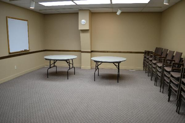 Meeting room at Hudson Street Hall with tables, chairs, and white board